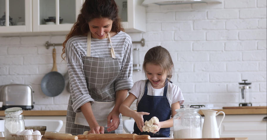 Loving happy mom teaching cute kid daughter learning kneading dough with rolling pin, funny child girl helping mother preparing cookies cooking baking pastry playing in modern kitchen at home