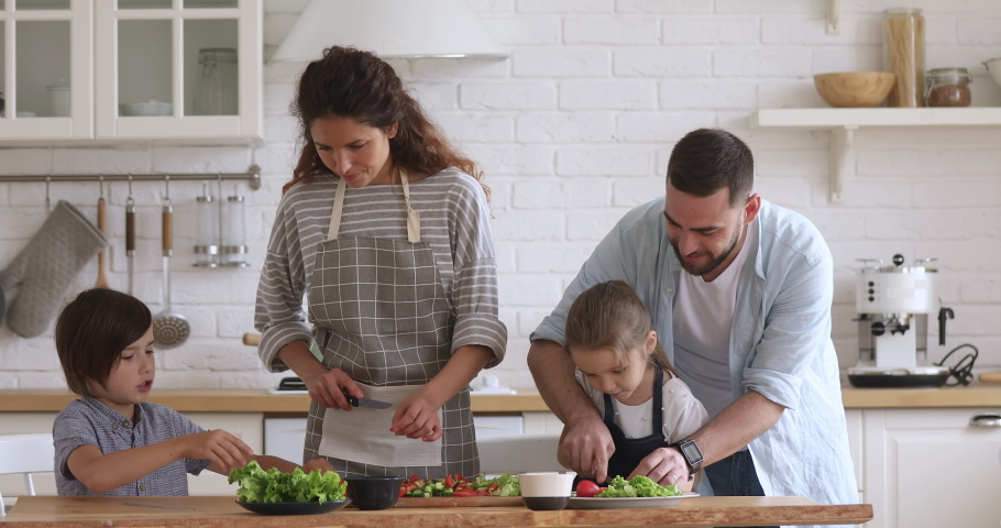 Happy family mom dad and kids siblings cooking together, young parents teaching children son daughter learning cutting fresh vegetable salad prepare healthy food in modern kitchen interior together