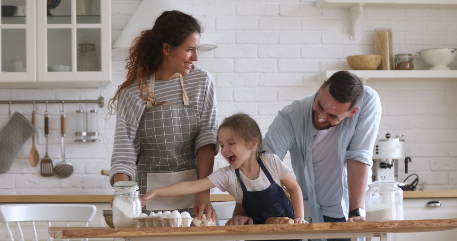 Happy family mom dad and kid daughter kneading dough baking pastry play with flour cooking together, young parents teaching child girl learning prepare cookies laughing having fun in modern kitchen