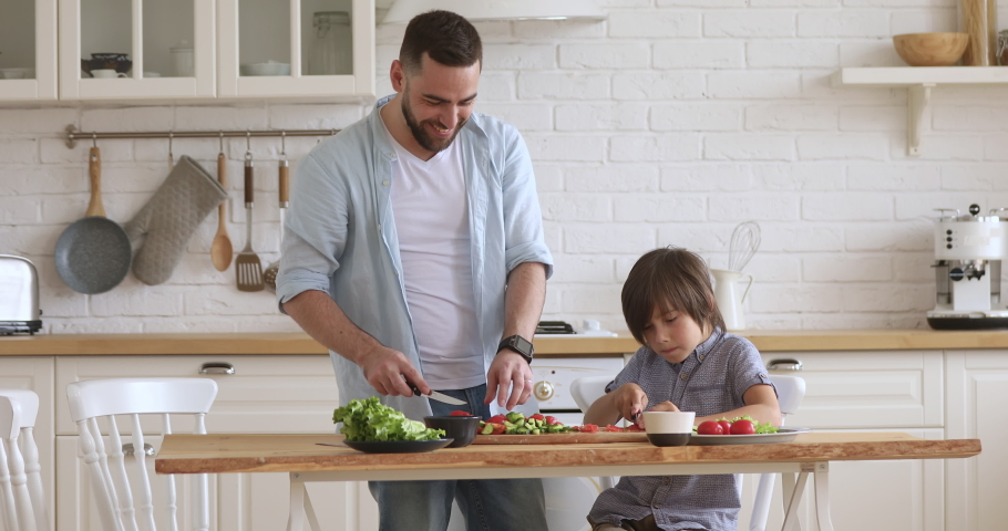 School boy son helping young happy father cutting fresh vegetables for healthy salad in modern kitchen interior, smiling dad teaching child learning cooking preparing dinner meal together at home