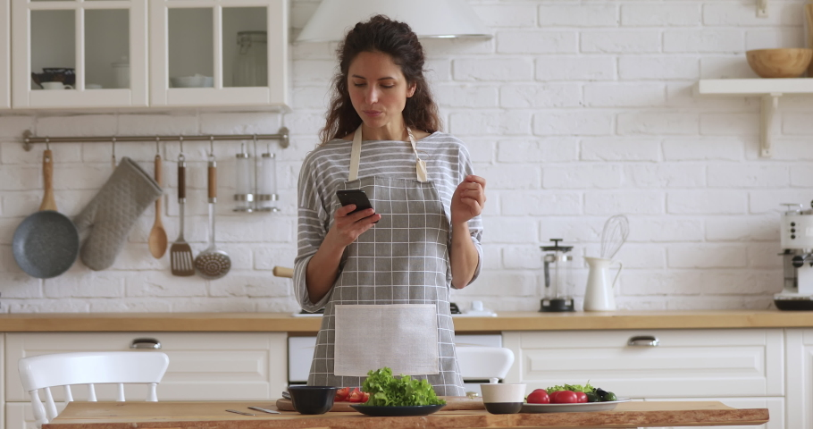 Happy young woman preparing vegetable meal searching checking online vegan recipe in smartphone, smiling vegetarian girl cooking healthy food salad using mobile cookbook menu apps in modern kitchen