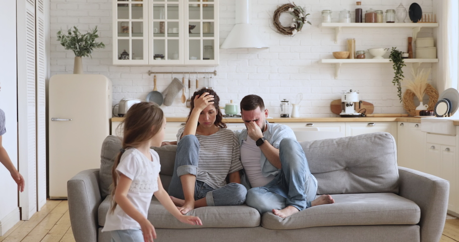 Frustrated stressed parents having headache feel tired annoyed exhausted about noisy active kids playing at home, upset disturbed couple mom dad fatigued of difficult disobedient misbehaving children | Shutterstock HD Video #1037333498