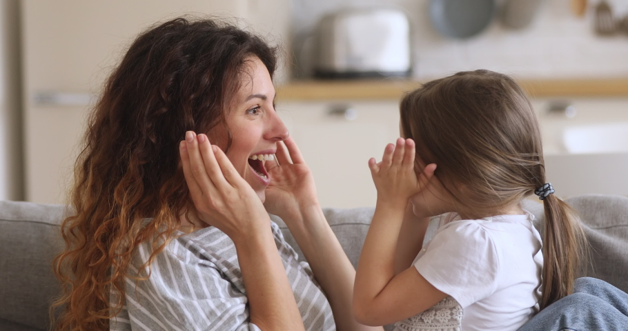 Happy playful young mother baby sitter and cute funny little kid child daughter playing peek a boo game cover face with hands hiding having fun together laughing bonding cuddling sit on sofa at home