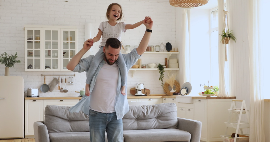 Loving young dad carrying cute little kid daughter giving piggyback ride at home, happy funny small girl sitting on father shoulder playing carrying child bonding having fun laughing in kitchen room