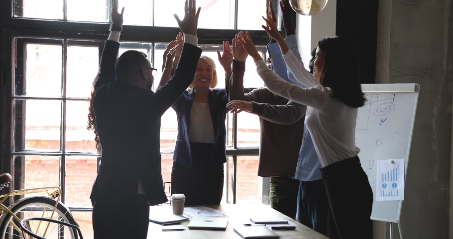 Happy multiracial business people with older mentor leader stack hands together at group meeting celebrate corporate victory, help in teamwork partnership leadership, building successful team concept Royalty-Free Stock Footage #1037333570