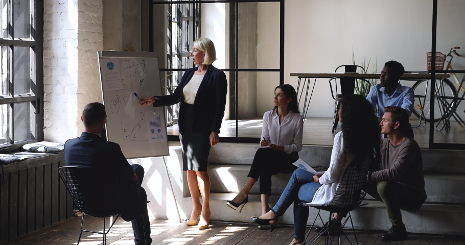 Confident female middle aged mature older business coach conference speaker manager give flip chart presentation at office meeting explain work plan teach diverse team at corporate workshop training Royalty-Free Stock Footage #1037333573