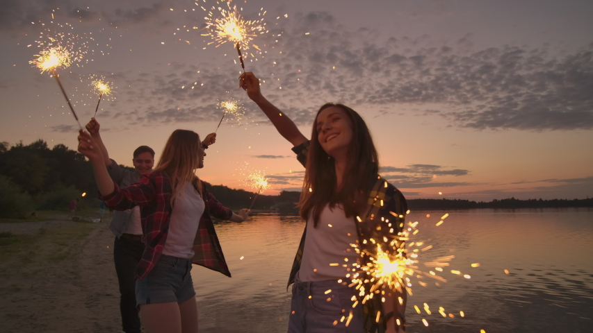 Cheerful male and female friends are running along the beach at sunset, holding sparkling fireworks and runaway lights in slow motion. Dancing and sunset party on the beach. Royalty-Free Stock Footage #1037334599