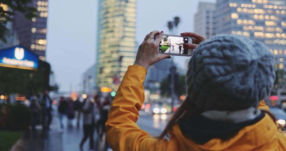 Young Woman Using Smartphone in the City, Taking Pictures. SLOW MOTION 4K. Girl using cell phone photography app, traffic lights background. Royalty-Free Stock Footage #1037334881