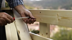 Adult carpenter craftsman with screwdriver screw the screw to fix the boards of a wooden fence. Housework do it yourself. Footage.