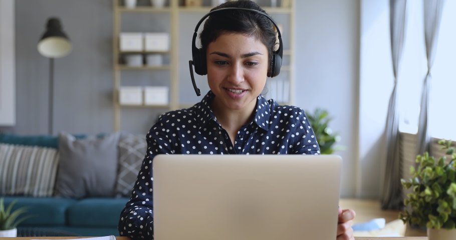 Smiling indian young business woman wear wireless headset video conference calling on laptop computer talk by webcam in online chat, customer support service and distance online teaching concept Royalty-Free Stock Footage #1037339309