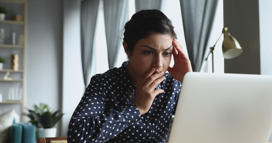 Young indian woman using looking at laptop computer at home office frustrated shocked after reading bad online news got email with failed test exam results feel upset stressed having problem concept
