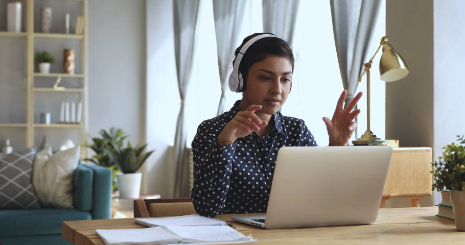 Focused indian woman distance teacher online tutor wear headphone conferencing on laptop communicate with student by webcam video call chat explain course help e learning computer education concept Royalty-Free Stock Footage #1037339321