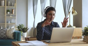 Focused indian woman distance teacher online tutor wear headphone conferencing on laptop communicate with student by webcam video call chat explain course help e learning computer education concept