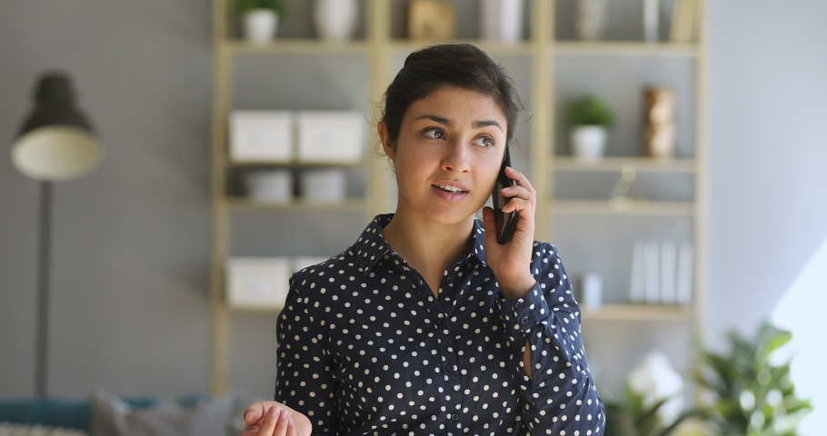 Young indian woman make call standing at home office, ethnic female entrepreneur holding cellphone having mobile conversation talking on the phone speaking communicating by smartphone indoors