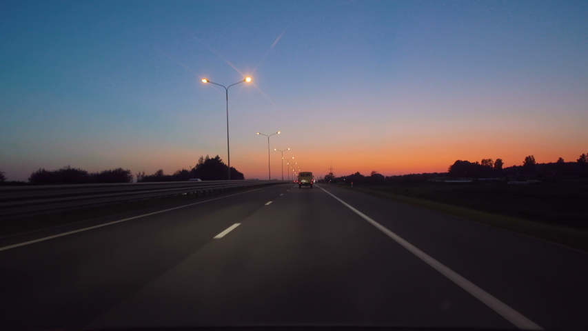 Driving Car POV On Freeway In Of Night In With Little Traffic After Sunset. Evening Sunset Street Lights. Night, Camera In Front, Windshield Reference. Driving Car On Highway At Dark 4K POV.