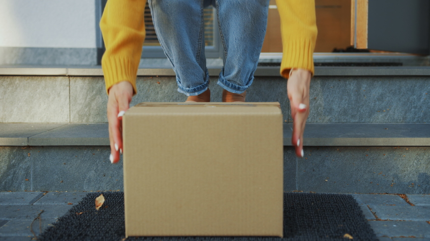Contactless Delivery of Internet Ordered Goods, Cardboard Box Package on the Door Step, Anonymous Woman Walks out of the Front Door and Picks-up Her Postal Parcel. Safe No Contact Delivery #1037351165