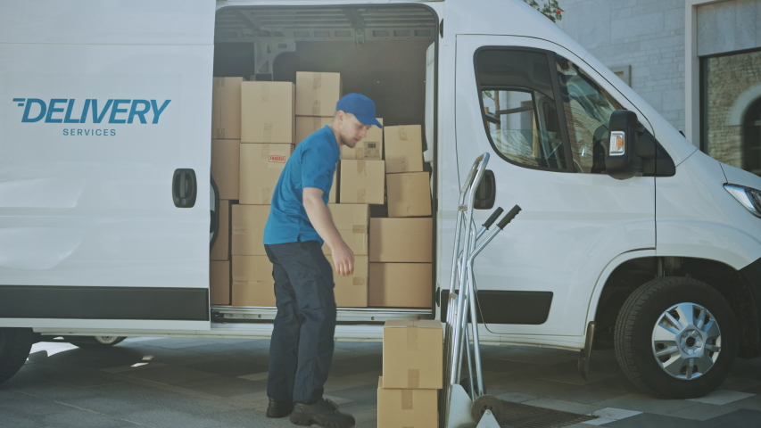 Delivery Man Uses Hand Truck Trolley Full of Cardboard Boxes and Packages, Loads Parcels into Truck / Van. Professional Courier / Loader helping you Move, Delivering Your Purchased Items Efficiently Royalty-Free Stock Footage #1037351195