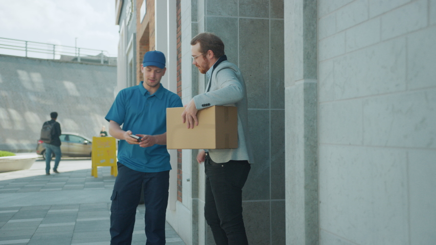 Delivery Man Pushes Hand Truck Trolley Full of Cardboard Boxes Hands Package to a Customer, Who then Signs Electronic POD Device. Courier Delivers Parcel to Man in Business District. Following Shot | Shutterstock HD Video #1037351207