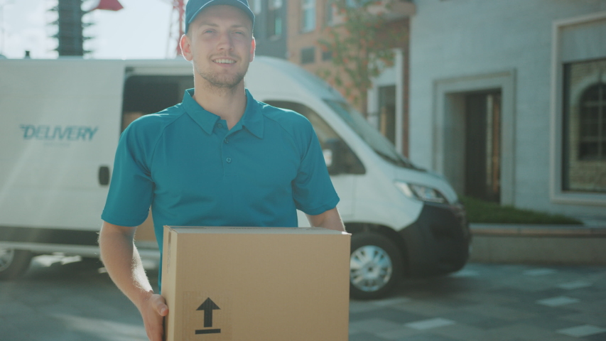 Handsome Courier Takes Cardboard Box Package out of Delivery Van Walks Through Modern Stylish Business District. Courier On the Way to Deliver Postal Parcel to a Client. Shot on RED EPIC-W 8K
