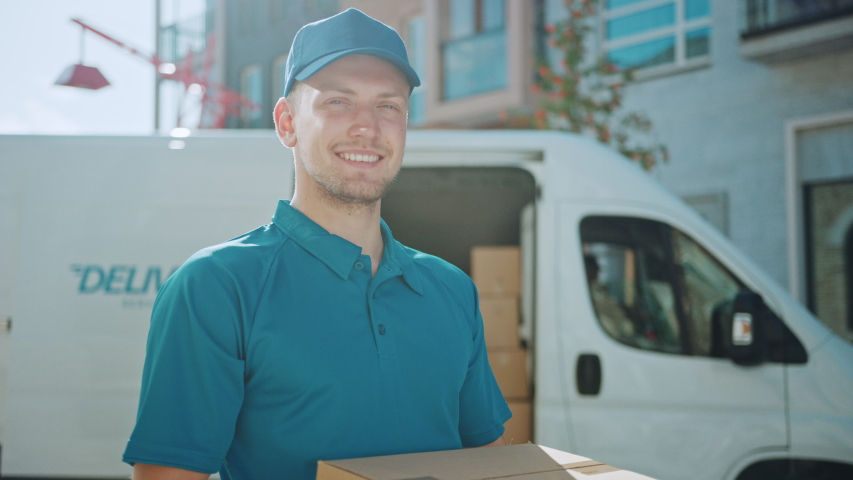 Portrait of the Handsome Delivery Man Holds Cardboard Box Package Standing in the Modern Stylish Business District with Delivery Van in the Background. Smiling Courier On the Way to Deliver Parcel Royalty-Free Stock Footage #1037351228
