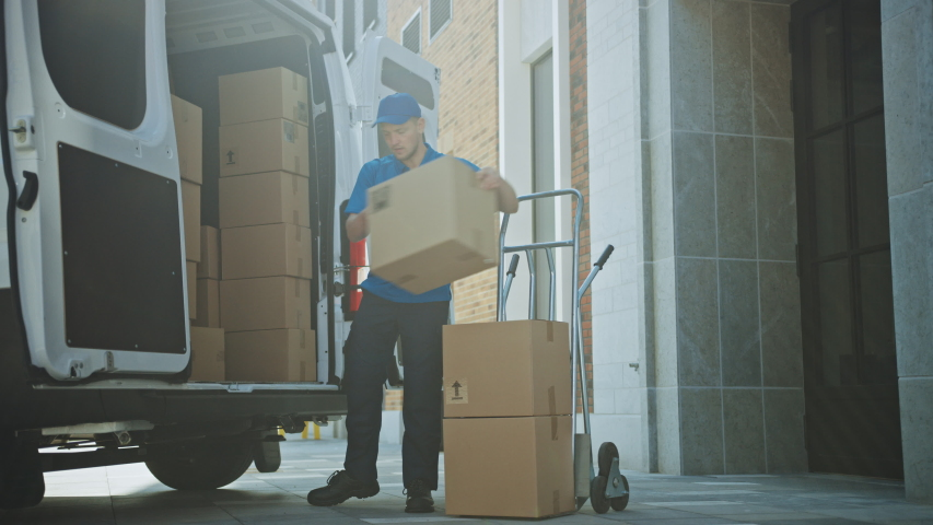 Delivery Man Uses Hand Truck Trolley Full of Cardboard Boxes and Packages, Loads Parcels into Truck / Van. Professional Courier / Loader helping you Move, Delivering Your Purchased Items Efficiently Royalty-Free Stock Footage #1037351288