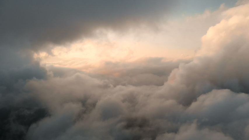 Aerial view flying through cumulus thunderclouds at sunset. Gold colored sunset cloudiness in high contrast. Real sky. The concept of dreams and weather forecast