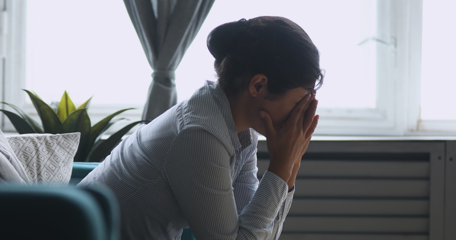 Depressed worried sad indian girl sit alone at home concerned about problem, upset desperate young woman feeling weak frustrated lonely jealous anxious regret mistake or abortion concept, side view