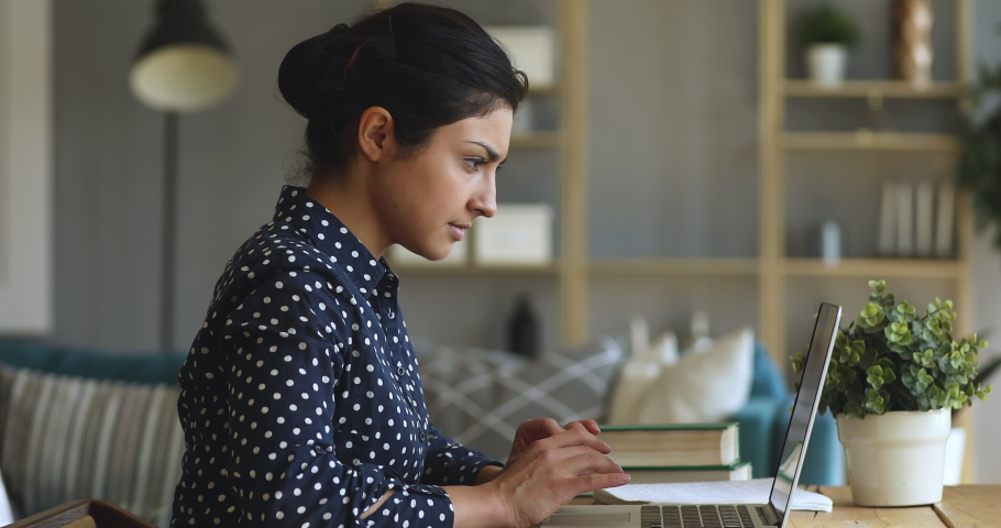 Focused young indian woman college university student doing homework assignment using laptop computer typing studying e learning on pc technology sit at home desk, distance online education concept Royalty-Free Stock Footage #1037352938