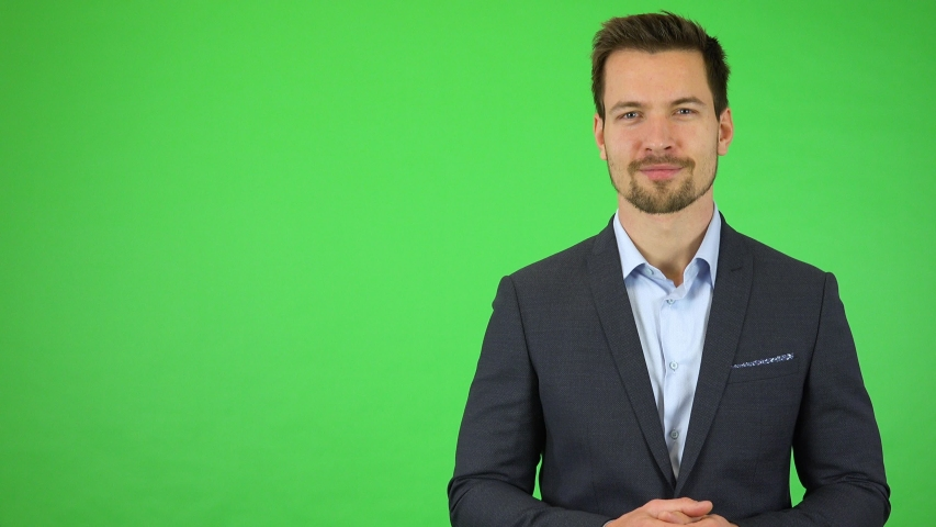 A young handsome businessman talks to the camera with a smile - green screen studio