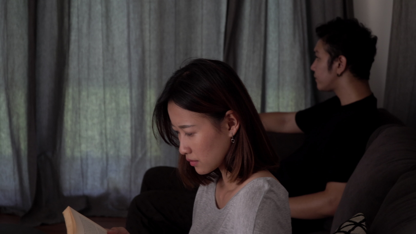 4K Dolly shot unhappy young asian couple sitting on sofa after quarrel fight at home and not talking together. Unhappy man and woman couple having a relationship conflict and thinking of break up. | Shutterstock HD Video #1037354963