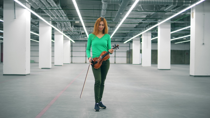 Female fiddler holds a violin and looks at camera, smiling. | Shutterstock HD Video #1037355119