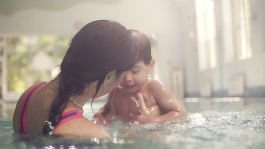 Cute baby having swimming lesson with his mother. Mother teaching her son to swim in the swimming pool. Young mom takes her son and embraces him. Indoors swimming pool #1037359406