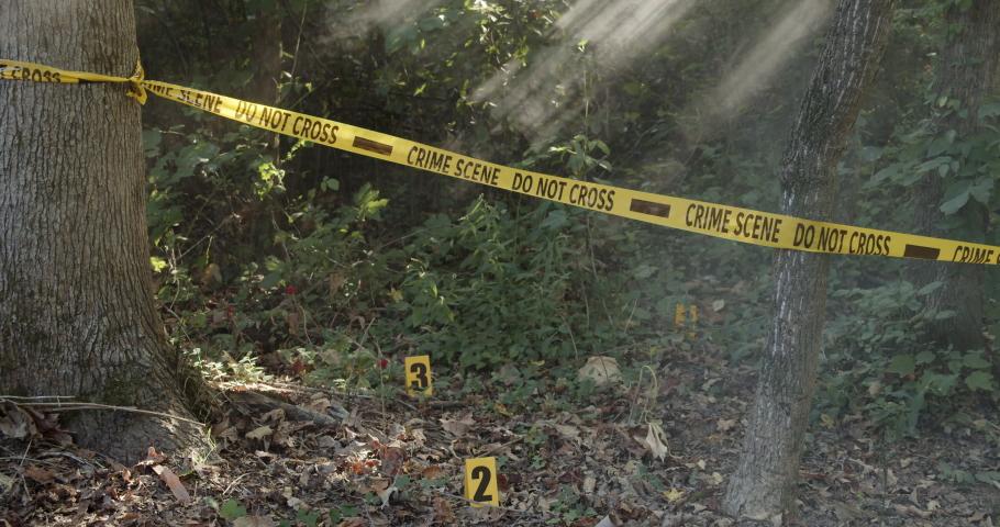 Police crime scene do not cross tape in the woods at the scene o the crime.