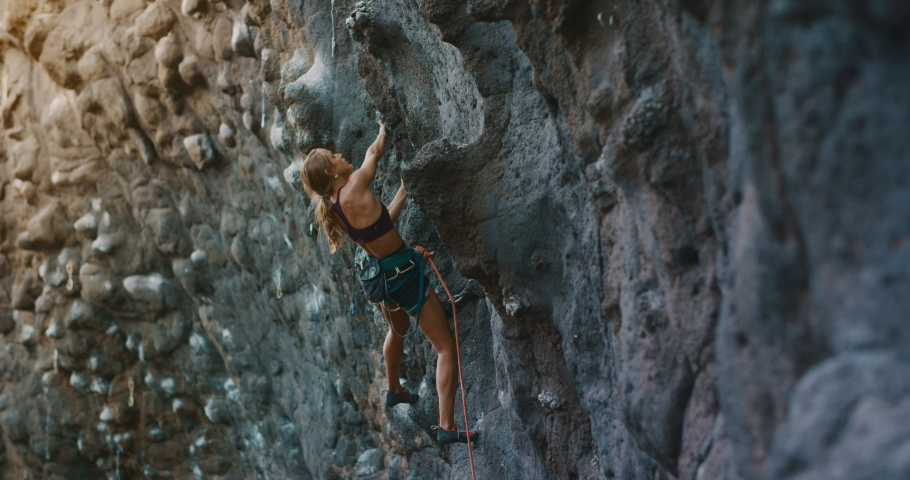Young fit woman lead rock climbing on sport route, outdoors rock climbing, cinematic slow motion rock climbing moments