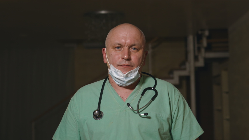 Healthcare and medical doctor portrait with stethoscope. Stands in green hospital uniform and puts on surgical face mask | Shutterstock HD Video #1037380406