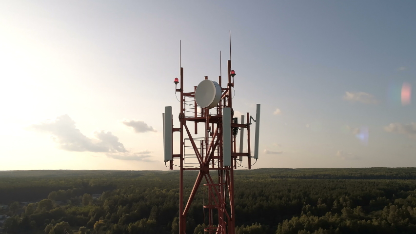 Closeup aerial shot around of telecommunication tower in a rural location. Telecom tower antennas and satellite transmits the signals of cellular 5g 4g mobile signals to the consumers and smartphones.