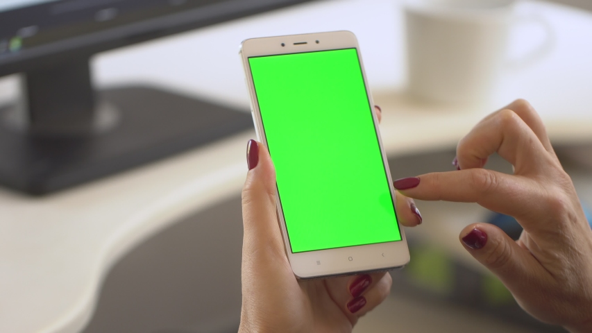 Business woman using smartphone viewing green screen on mobile phone browsing chroma key online watching enjoying drinking coffee reading social media close up hands. Shopping on the Internet. | Shutterstock HD Video #1037389112