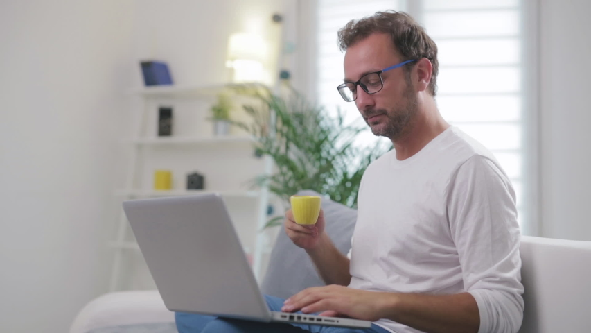Man listening to music and using laptop in the living room. | Shutterstock HD Video #1037397485
