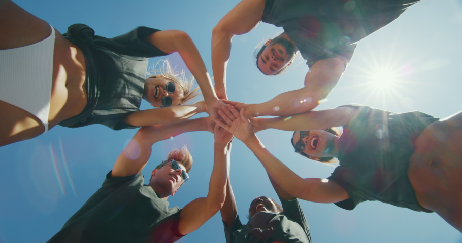 Slow motion close up of a team of young volunteers are satisfied with picking up a plastic litter on a beach with a sea to protect an environment.   Shutterstock HD Video #1037400326