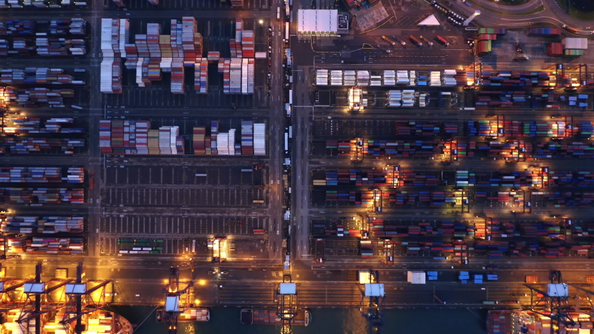 Aerial top view of container cargo ship in the export and import business and logistics international goods in urban city. Shipping to the harbor by crane in Victoria Harbour, Hong Kong City at night. | Shutterstock HD Video #1037405360
