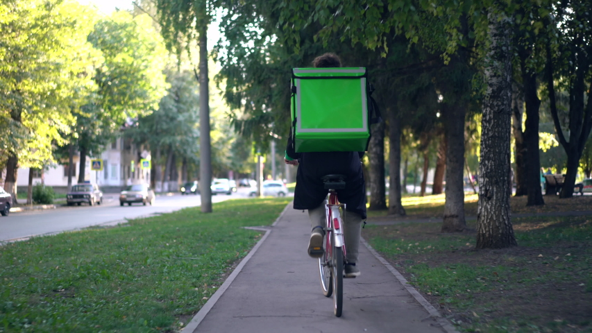 Delivery man with green backpack rides a bicycle through the city with food delivery. | Shutterstock HD Video #1037410598