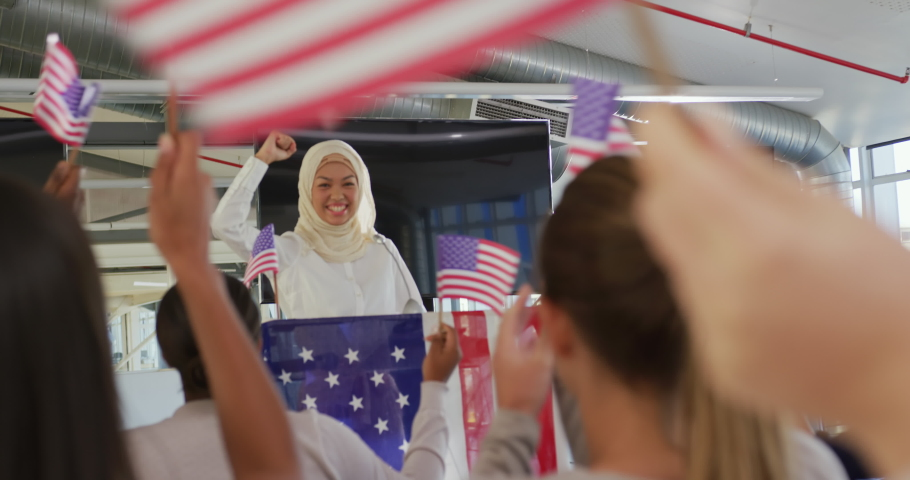 Front view of a smiling young Asian woman wearing a hijab standing at a lectern decorated with a US flag and raising her fist in triumph at a political rally, with the audience seen from the back