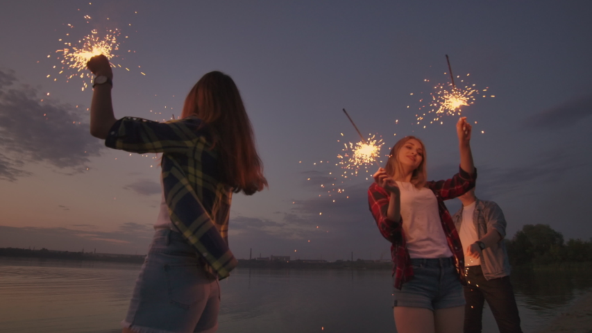 Cheerful male and female friends are running along the beach at sunset, holding sparkling fireworks and runaway lights in slow motion. Dancing and sunset party on the beach. Royalty-Free Stock Footage #1037413589