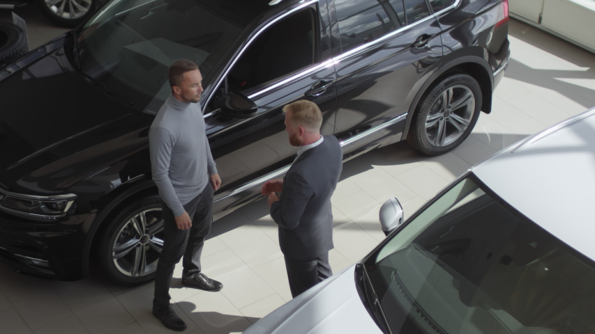 High angle shot of salesman shaking hands with male customer, helping him to sit into new car and giving key after selling auto in dealership showroom