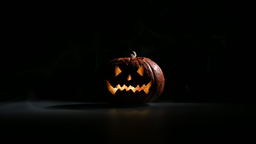 Halloween, orange pumpkin with a scary luminous face on a dark background. Gray thick smoke comes out. | Shutterstock HD Video #1037424608