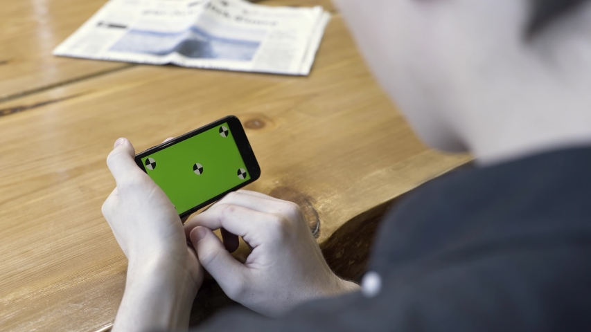 Smartphone horizontal orientation with a green screen: shot over the shoulder of a young man. Stock Footage. Man sitting at the table, tapping and scrolling on the chromakey of the phone.   Shutterstock HD Video #1037425157
