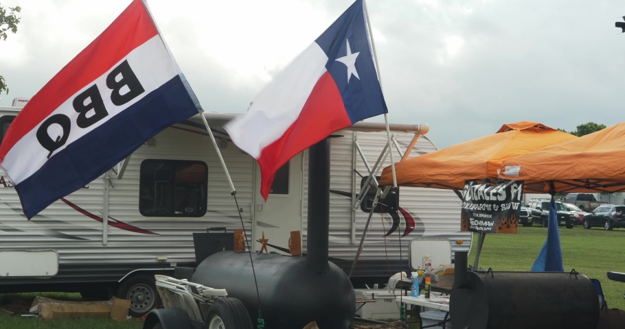 Lockhart , Texas / United States - 09 02 2019: BBQ Flag and Texas Flag waving in front of a BBQ Team's RV and Smokers