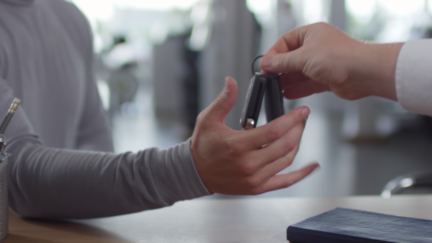 Close up shot of hands of man sitting at table in auto showroom, taking car key from salesman and walking away | Shutterstock HD Video #1037437001