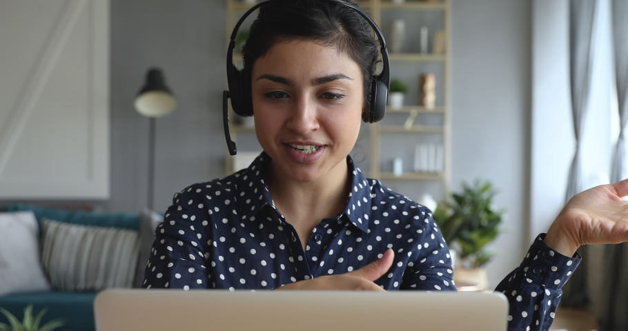 Happy indian young woman wear headset communicating by conference call speak looking at computer at home office, video chat job interview or distance language course class with online teacher concept | Shutterstock HD Video #1037437004