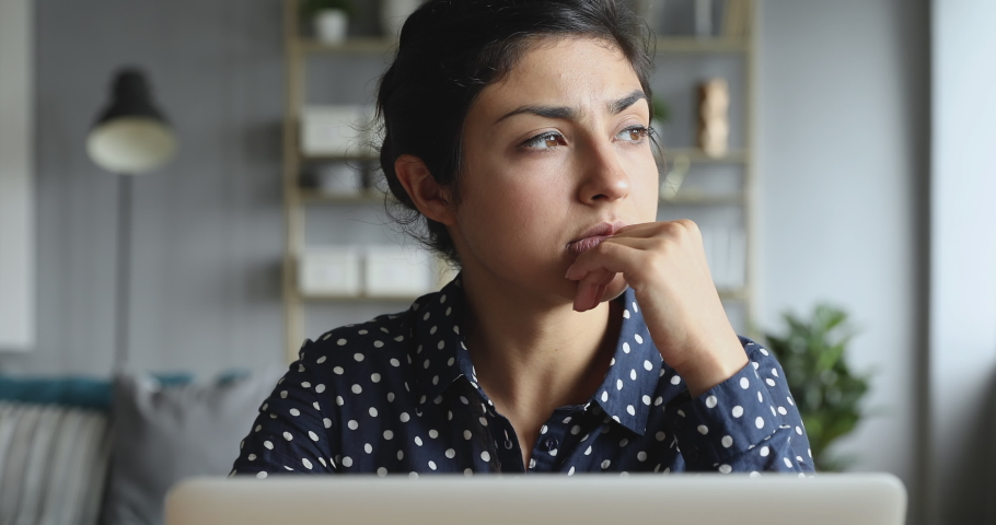 Thoughtful concerned indian woman working on laptop computer looking away thinking solving problem at home office, serious woman search for inspiration make decision feel lack of ideas, close up view Royalty-Free Stock Footage #1037437007